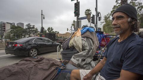 Los autos pasan junto a un hombre que vive en las calles en Los Á...