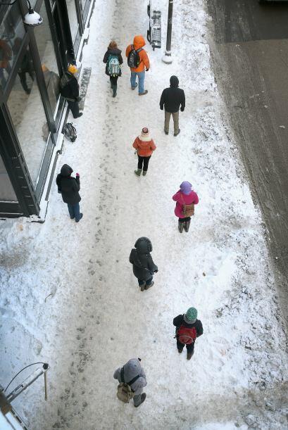 Viajeros esperan en una acera helada en temperaturas bajo cero para abor...