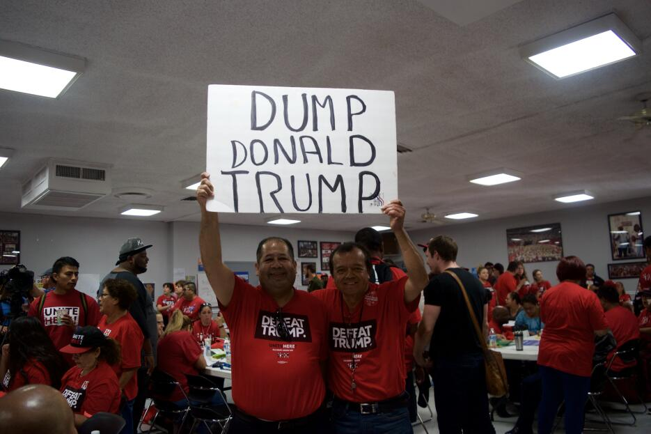 """Con camisetas de """"Derrota a Trump"""" y carteles de """"Desecha..."""