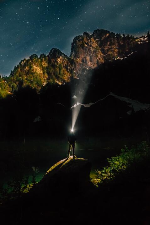 Un hombre con lámpara de cabeza posado sobre una roca mirando a l...
