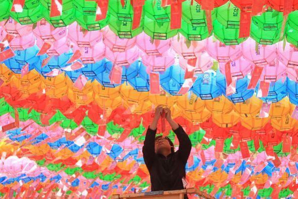 Un budista surcoreano cuelga linternas de colores para celebrar el próxi...