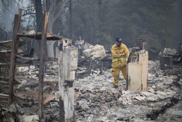 Un bombero observa los restos de un cajero automático en un mercado al n...