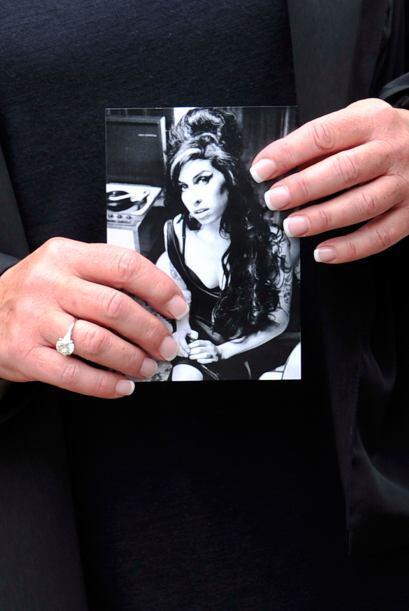Un personaje del cortejo fúnebre sostiene una foto de Amy Winehou...