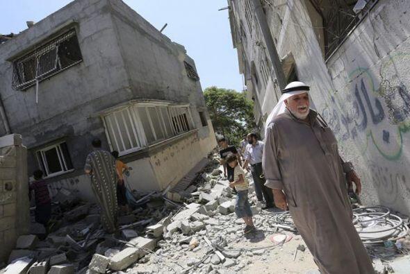 Un grupo de vecinos palestinos camina entre los escombros de las casas d...