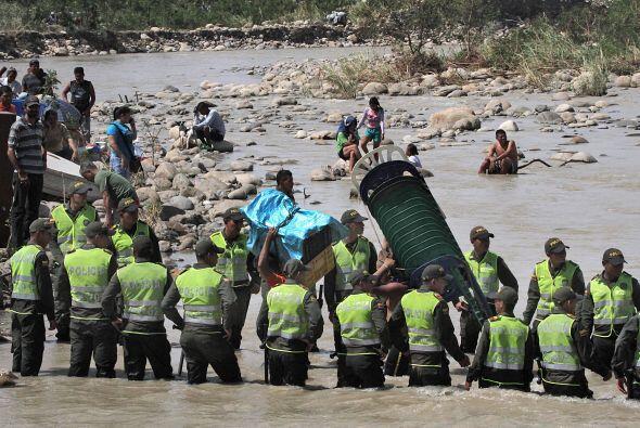 Los colombianos deportados llevan sus pertenencias a través dle río.