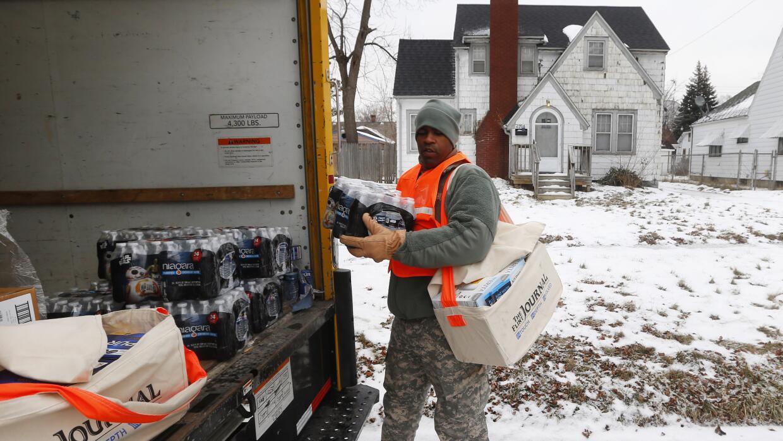 Este guardia nacional reparte agua embotellada a los habitantes de Flint