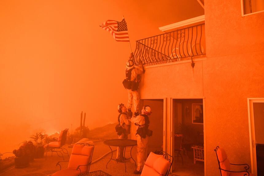 Los bomberos bajan una bandera mientras llamas de fuego Wall se acercan...