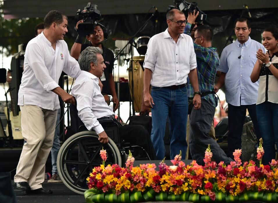 Ecuadorean President Rafael Correa (L), pushes candidate for the preside...
