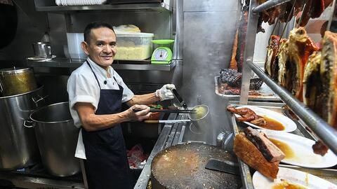 El chef Chan Hon Meng prepara alimentos en su restaurante callejero 'Hon...