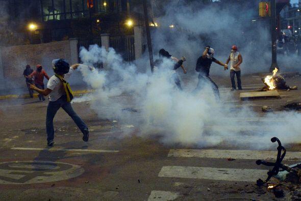 Con barricadas en llamas y lanzando piedras a la policía para que...