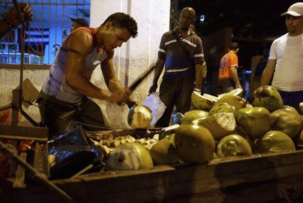 Un vendedor de cocos ofrece la fruta a los cubanos que regresan de traba...