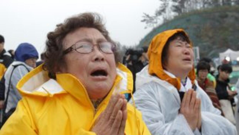 Familiares de jóvenes atrapados en el ferry hundido en Corea del Sur rez...