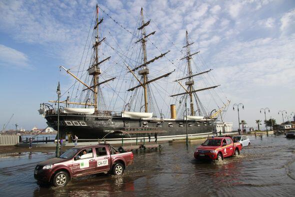 Diversos vehículos transitan por una calle inundada frente a la r...