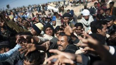 Milies de libios y trabajadores extranjeros huyen de Libia a causa de la...