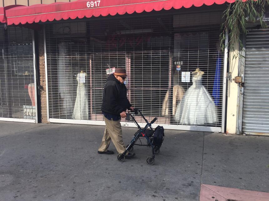Un anciano camina frente a una tienda de ropa cerrada en el bulevar Paci...