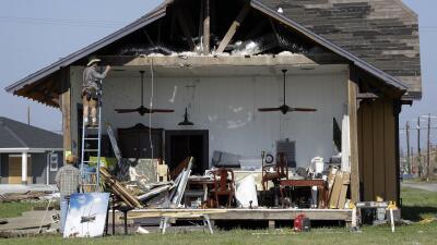 Varios trabajadores comienzan a reparar un muro de una casa que Harvey d...