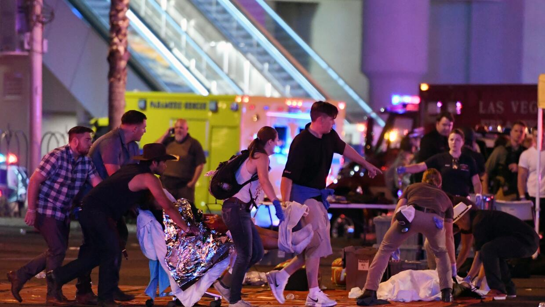 Un grupo de personas traslada a una persona herida hacia la ambulancia t...
