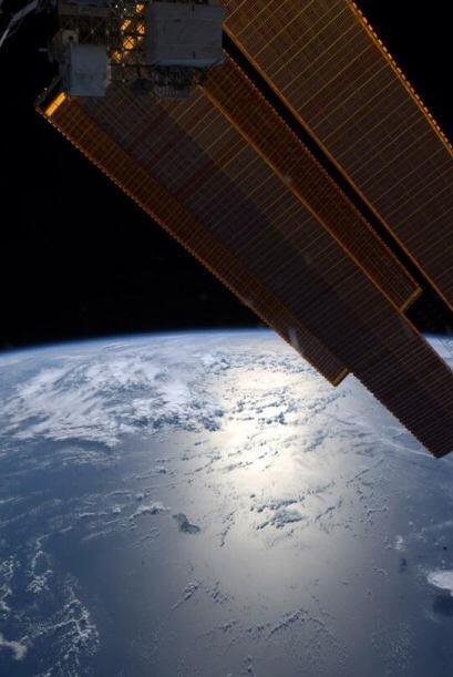 Buenas noches desde la ISS. Los paneles solares brillan al acercarse a A...