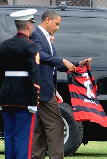 Obama observando el regalo, tal vez comprobando si el talle es el adecua...