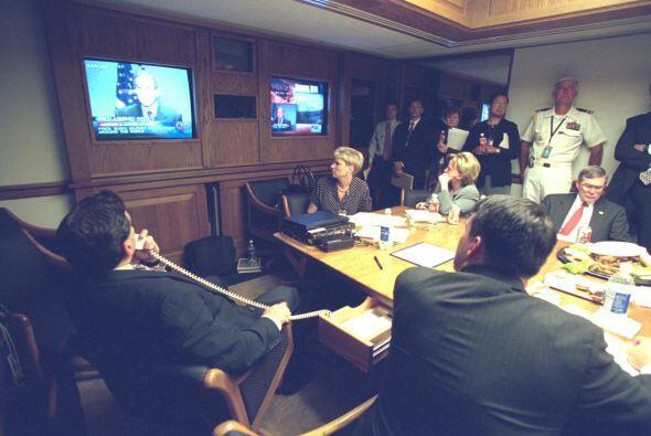 Destacados miembros del Gobierno miran a Bush haciendo una declaración e...