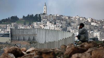 Un hombre junto al muro que separa el barrio palestino al Al-Tur de Jeru...