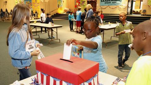 Estudiantes de primaria simulan una votación durante el día de las elecc...